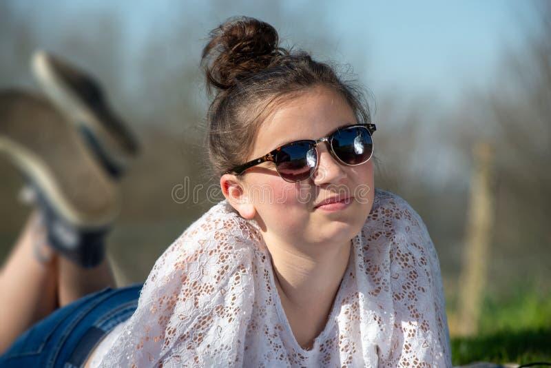 Portrait d'une fille de jeune adolescent avec des lunettes de soleil extérieures photos libres de droits