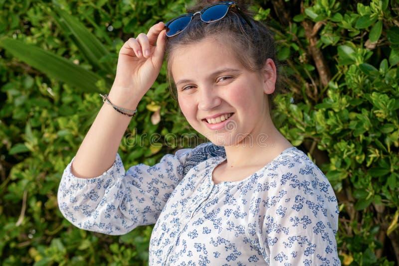 Portrait d'une fille de jeune adolescent avec des lunettes de soleil extérieures photos stock