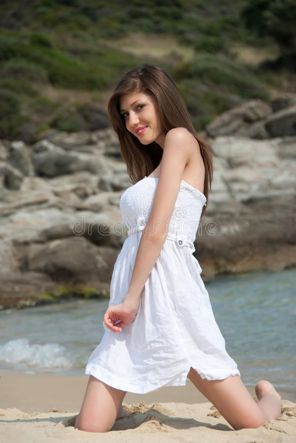 Portrait d'une fille de l'adolescence avec la robe blanche à la plage photos stock