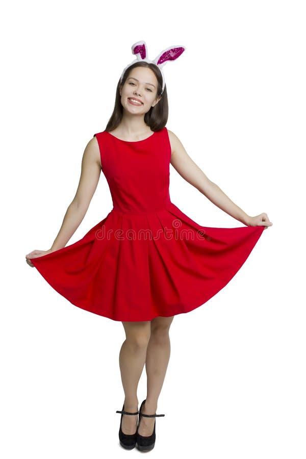 Portrait d'une fille de sourire de brune sur le tir blanc de studio dans le chapeau de Santa Claus et la robe rouge image libre de droits