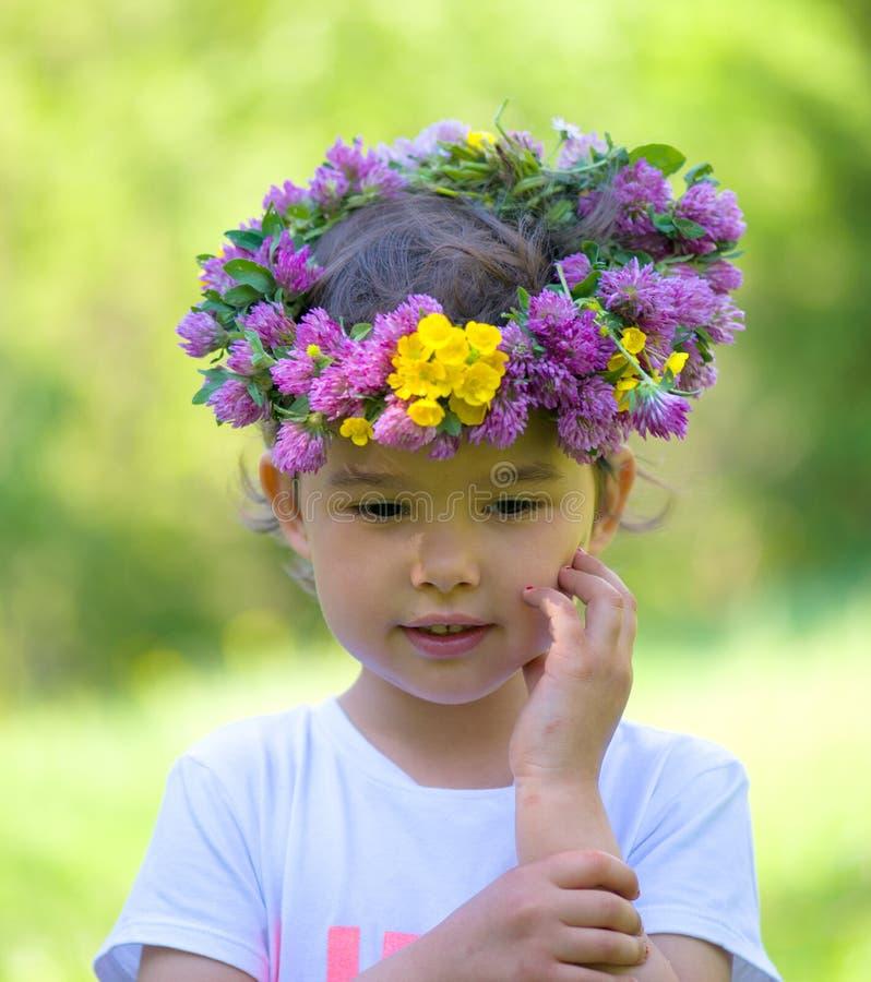 Portrait d'une fille gaie avec une guirlande des fleurs image libre de droits