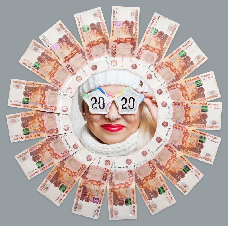 Portrait d'une fille gaie en verres avec l'inscription 2020 au centre du cercle de cinq mille factures photo libre de droits