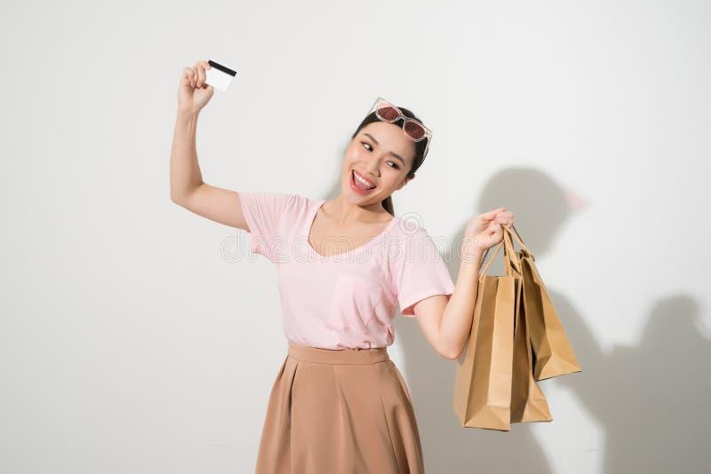 Portrait d'une fille heureuse ?tonn?e tenant des sacs ? provisions et montrant la carte de cr?dit tout en regardant la cam?ra d'i photo stock