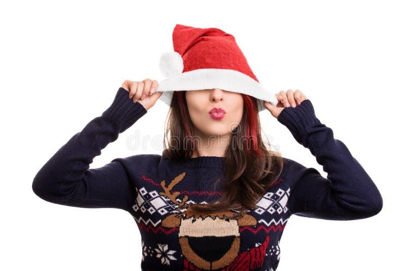 Portrait d'une fille mettant sur le chapeau d'une Santa au-dessus de son visage image stock