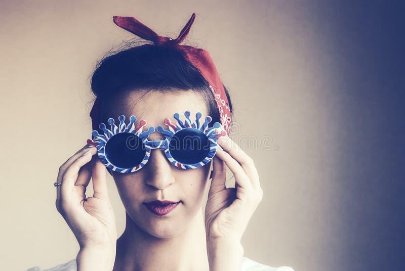 Portrait d'une fille mignonne dans des lunettes de soleil drôles photos stock