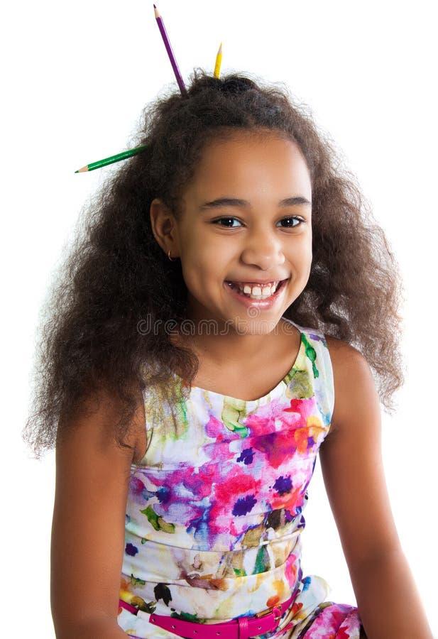 Portrait d'une fille noire mignonne sur un fond blanc Émotions humaines positives Les sourires d'enfant Crayons multicolores coll image libre de droits