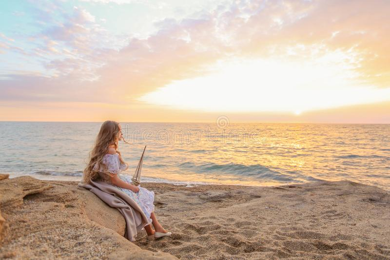 Portrait d'une fille près de la mer se reposant sur les roches avec un bateau de jouet dans des mains photos libres de droits
