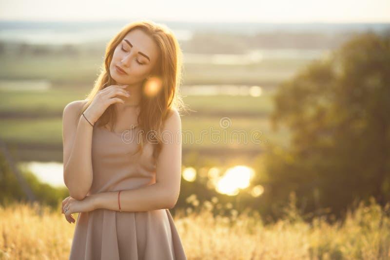 Portrait d'une fille rêveuse dans un domaine au coucher du soleil, une jeune femme appréciant la nature photo libre de droits