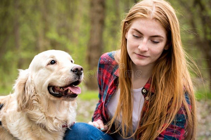 Portrait d'une fille rousse avec un chien images stock