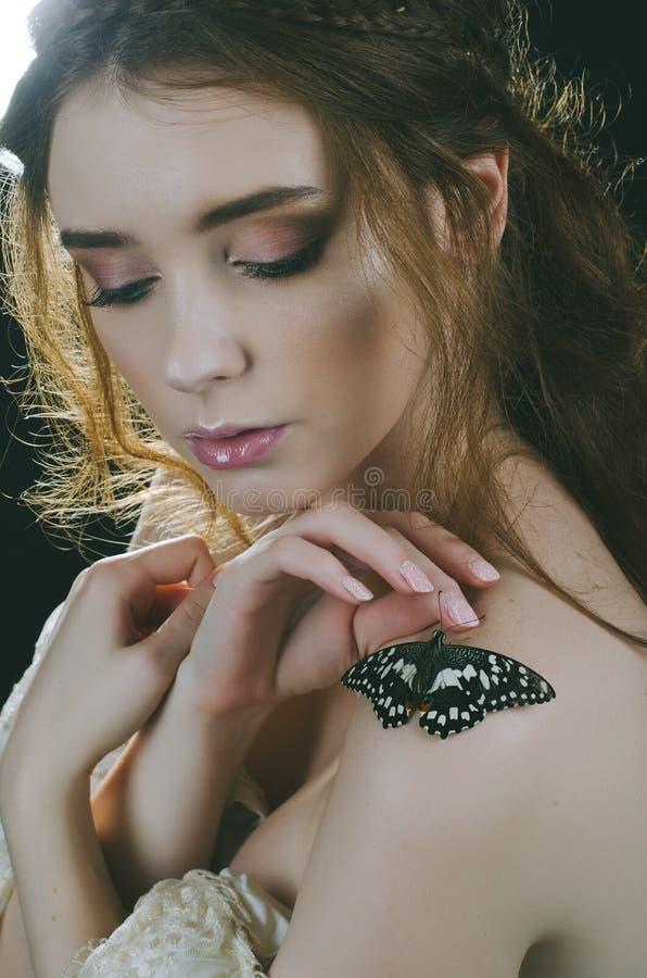 Portrait d'une fille rousse dans une robe d'or de vintage, dans le contre-jour avec un papillon sur son épaule Princesse de vinta images stock