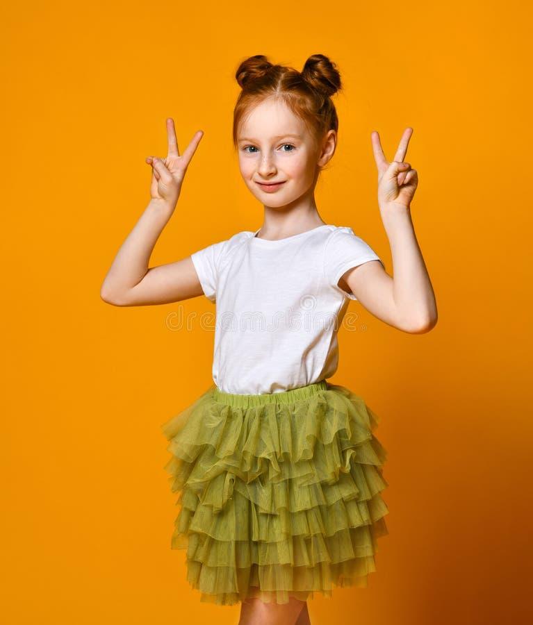 Portrait d'une fille rousse magnifique regardant la caméra avec un sourire et montrant le signe de paix avec des doigts photos libres de droits