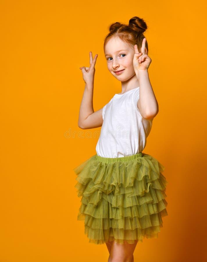 Portrait d'une fille rousse magnifique regardant la cam?ra avec un sourire et montrant le signe de paix avec des doigts image libre de droits