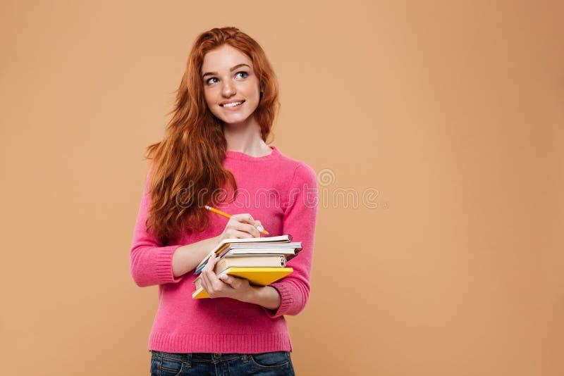 Portrait d'une fille rousse réfléchie heureuse tenant des livres images libres de droits