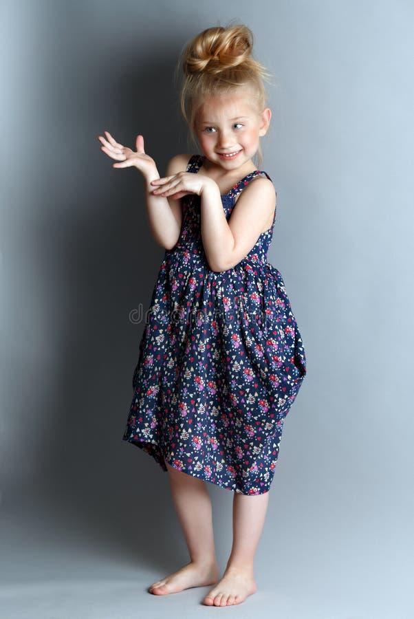 Portrait d'une fille timide sur un fond bleu photographie stock libre de droits