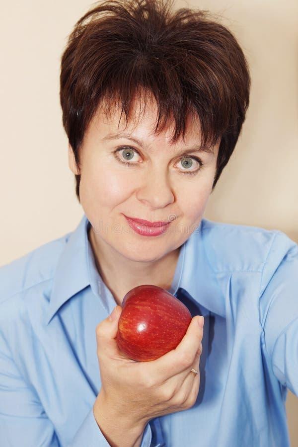 Portrait d'une gentille femme avec la pomme image stock
