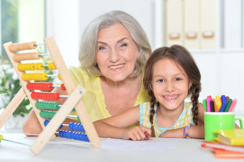Portrait d'une grand-mère et d'une petite-fille comptant à la maison photo libre de droits