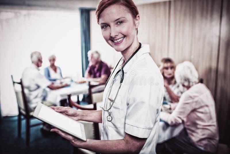 Portrait d'une infirmière avec le comprimé numérique images stock