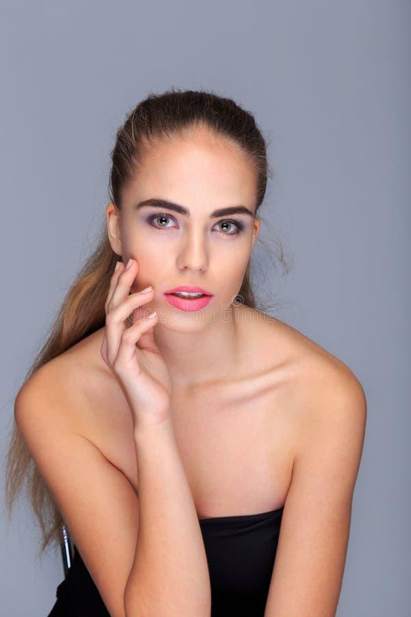Portrait d'une jeune, attirante femme, modèle, sur un fond gris-clair, cosmétiques photographie stock