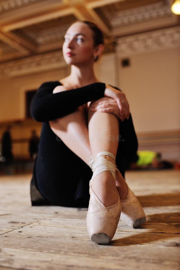 Portrait d'une jeune ballerine mignonne s'asseyant sur un plancher en bois image libre de droits