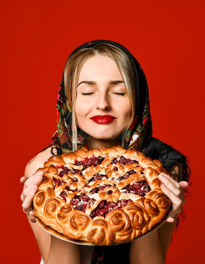 Portrait d'une jeune belle blonde dans le foulard tenant un tarte fait maison délicieux de baie images stock
