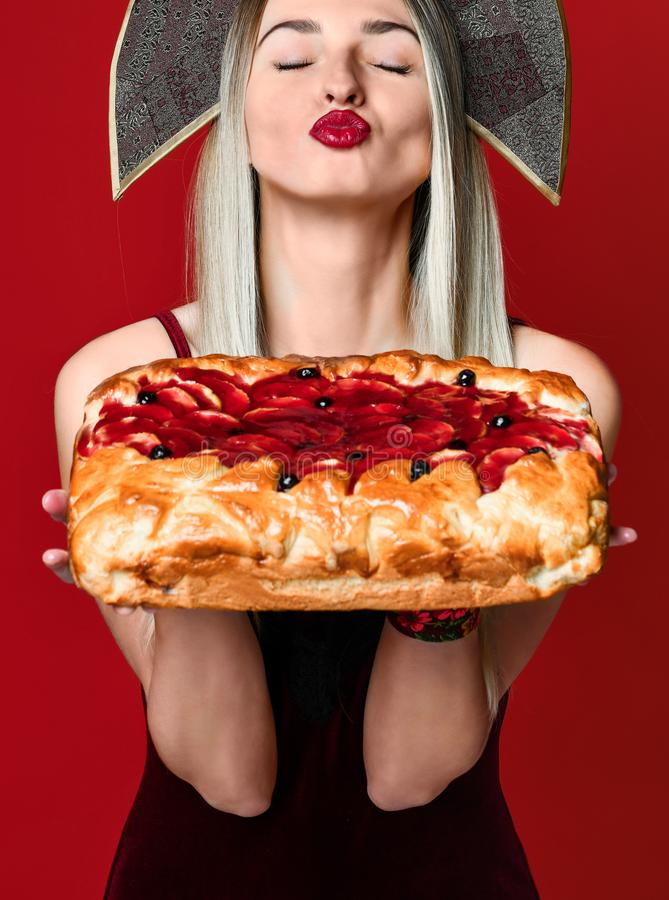 Portrait d'une jeune belle blonde dans le kokoshnik tenant une tarte aux cerises faite maison délicieuse photo stock