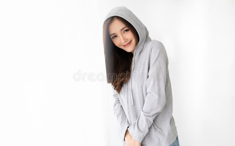 Portrait d'une jeune belle femme asiatique dans une position grise de hoodie près de la fenêtre détendant et regardant la caméra  images stock