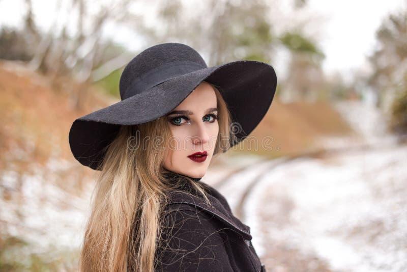 Portrait d'une jeune belle femme dans le rétro style de chapeau noir photos stock