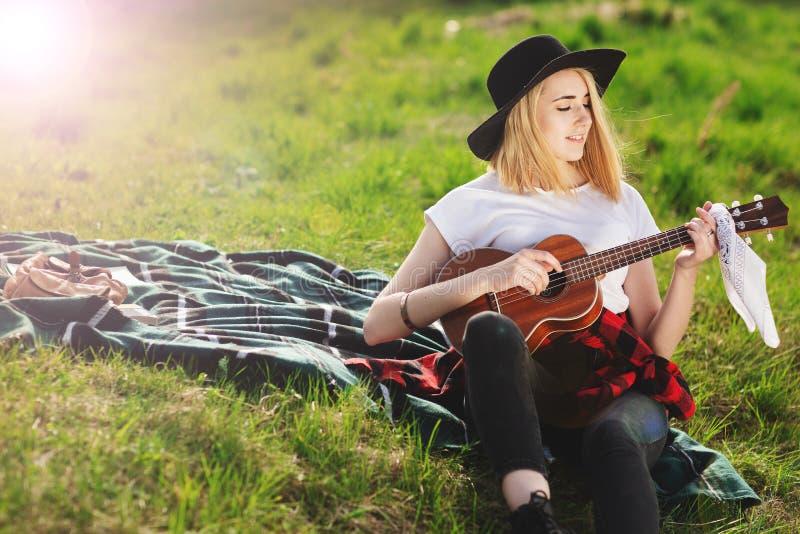 Portrait d'une jeune belle femme dans un chapeau noir Fille s'asseyant sur l'herbe et jouant la guitare images stock