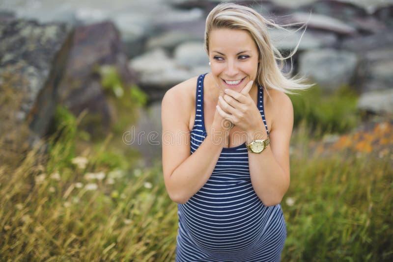 Portrait d'une jeune belle femme enceinte blonde du côté de la plage photographie stock libre de droits