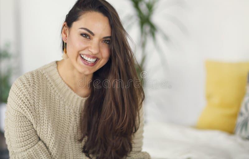 Portrait d'une jeune belle femme heureuse dans des habillements chauds ? la maison photographie stock