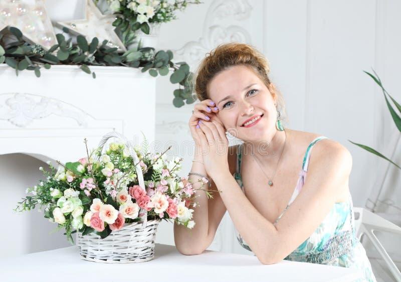 Portrait d'une jeune belle femme s'asseyant ? une table photos stock