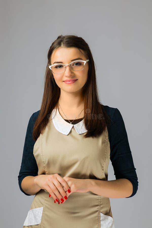Portrait d'une jeune belle fille avec de longs vêtements et verres de travail de port de cheveux foncés photo stock