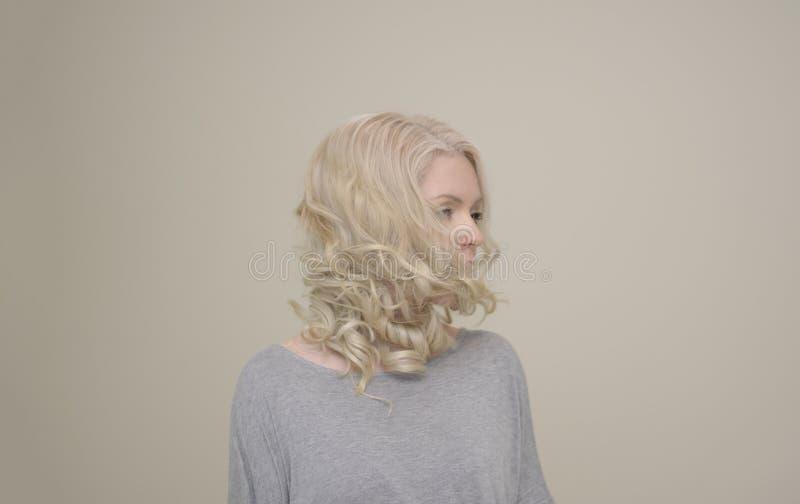 Portrait d'une jeune belle fille avec le vol de luxe de cheveux sur le fond clair images libres de droits