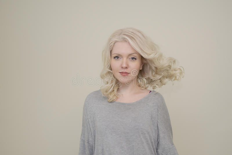 Portrait d'une jeune belle fille avec le vol de luxe de cheveux sur le fond clair photo libre de droits