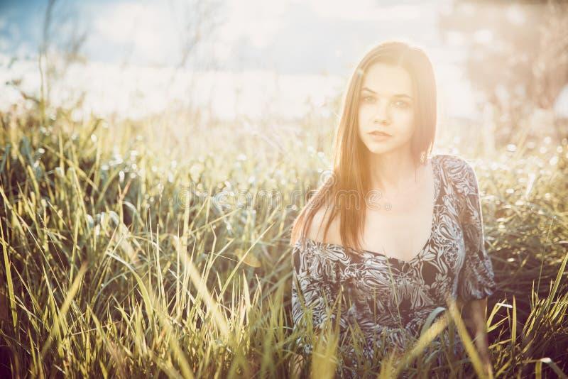 Portrait d'une jeune belle fille dans une robe se reposant dans le gra photos stock