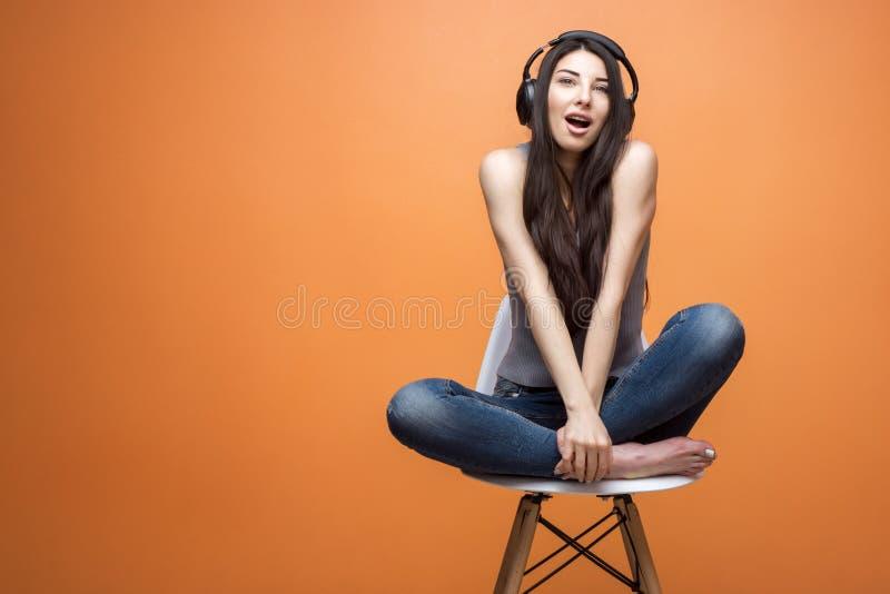 Portrait d'une jeune belle fille s'asseyant dans la chaise et écoutant la musique par le casque sur le fond orange photos libres de droits