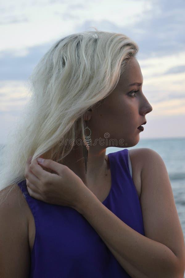 Portrait d'une jeune blonde dans le profil contre la mer images stock