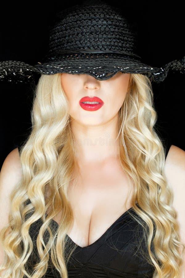 Portrait d'une jeune blonde dans un chapeau noir avec un decollete, au-dessus d'un fond noir Lèvres rouges lumineuses photos stock