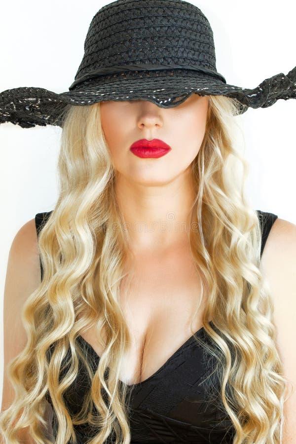 Portrait d'une jeune blonde dans un chapeau noir avec Decollete, sur le fond blanc Plan rapproché image stock