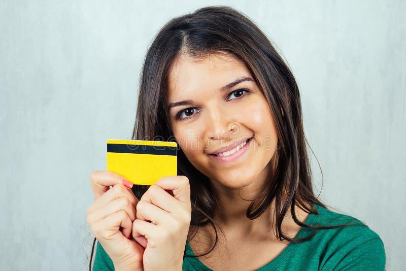 Portrait d'une jeune et belle brunette tenant une carte de crédit dans la main. concept de shopping et de crédit photo libre de droits
