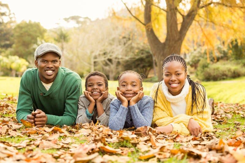 Portrait d'une jeune famille de sourire se situant dans des feuilles images stock