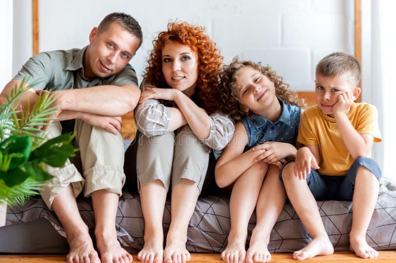 Portrait d'une jeune famille heureuse avec deux enfants dans la chambre ? coucher, photographie stock