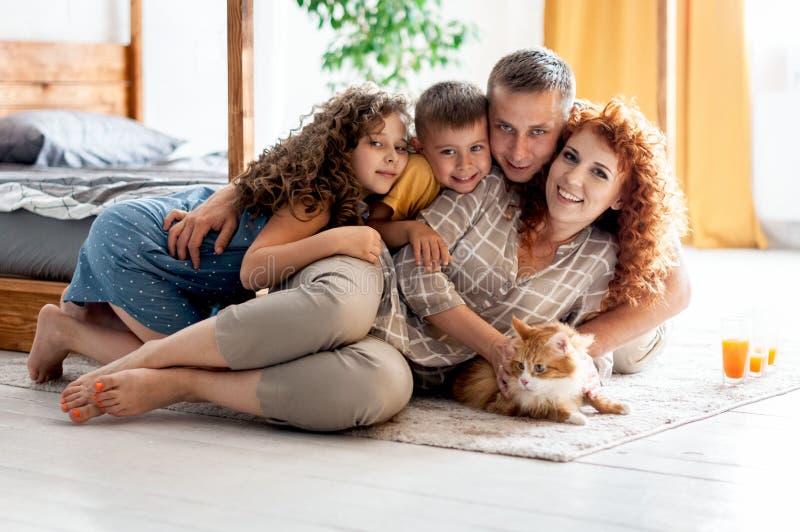 Portrait d'une jeune famille heureuse avec deux enfants et chat pelucheux rouge image libre de droits