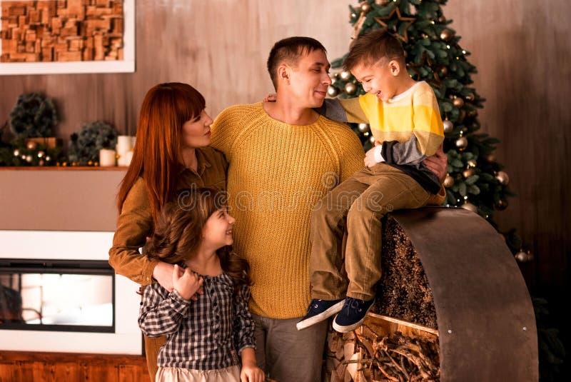 Portrait d'une jeune famille heureuse avec deux enfants sur le fond de l'arbre de Noël photo libre de droits