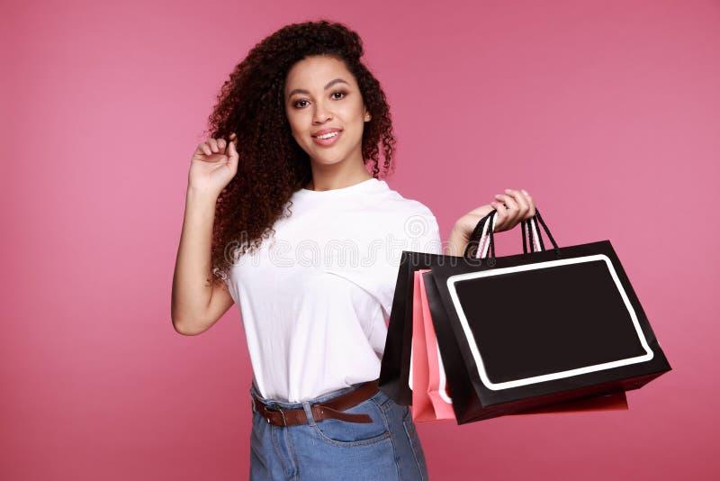 Portrait d'une jeune femme africaine enthousiaste tenant des sacs à provisions et montrant la carte de crédit au-dessus du fond b images stock