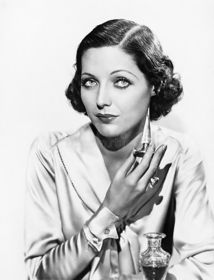 Portrait d'une jeune femme appliquant le parfum (toutes les personnes représentées ne sont pas plus long vivantes et aucun domain photo stock