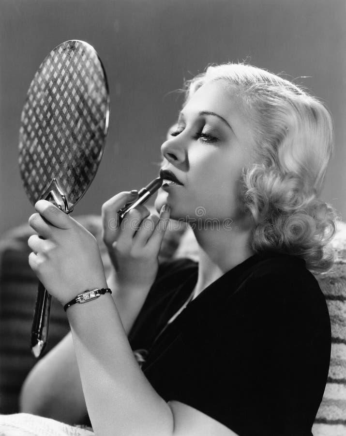 Portrait d'une jeune femme appliquant un rouge à lèvres sur ses lèvres (toutes les personnes représentées ne sont pas plus long v image libre de droits