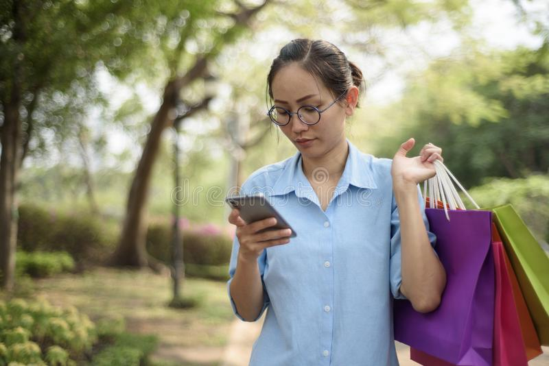 Portrait d'une jeune femme asiatique heureuse tenant des paniers et photos libres de droits