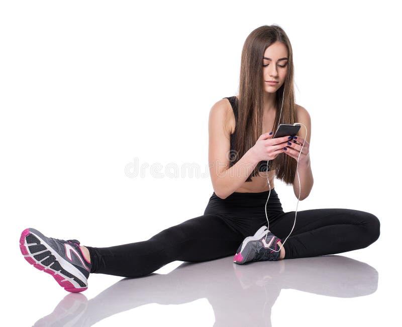 Portrait d'une jeune femme d'athlète écoutant la musique avec des écouteurs au-dessus du fond blanc Fille attirante de forme phys photos stock