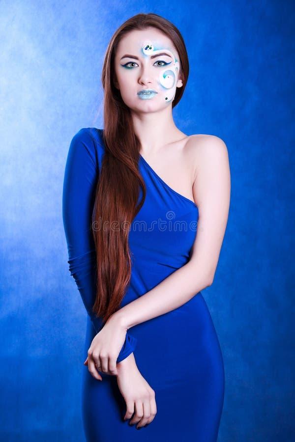 Portrait d'une jeune femme attirante avec un art bleu de visage photo stock